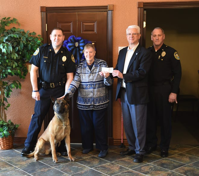 Lou Ann Wilcox recently made a donation to the Mountain Home Police Department towards the care and well-being of the city's K-9, Harmon. Wilcox, who splits her time between the Twin Lakes Area and Waukesha, Wis., also donated a dozen tennis balls and a 2020 calendar featuring a memorial photo of Benga, the city's former K-9 who passed away in November 2017. The calendar is produced by Vested Interest in K-9s, Inc., a nonprofit organization that helps provide bulletproof and stab-protective vests to law enforcement dogs. The body armor that Harmon currently wears was donated to the police department by Vested Interest in K-9s and bears an inscription in Benga's memory. Wilcox said she will pray that both Harmon and his handler, Sgt. Jonathan Griffin, will stay safe as they protect everyone in the community. For more information about the Vested Interest in K-9s program, visit them online at www.vik9s.org. Shown in the above photo are (left to right) Sgt. Jonathan Griffin, Harmon, Lou Ann Wilcox, Police Chief Carry Manuel and Lt. Eric Neal.