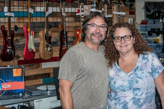 Lance and Tracy Lisenby in front of a wall of custom guitars hanging in Lisenby's Music Shop in Prattville.