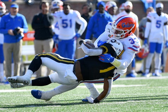 Florida Gators linebacker David Reese II (33) tackles Missouri Tigers running back Tyler Badie (1) during the second half of a game Nov. 16 at Memorial Stadium/Faurot Field in Columbia, Missouri.