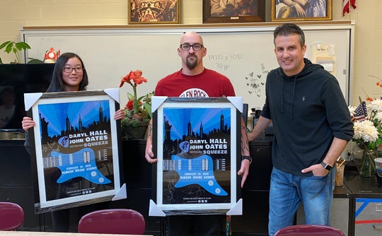Iris Chung, left, art teacher Scott Kupka and music agent Peter Papparlardo with Chung's poster for best-selling music duo Daryl Hall and John Oates.