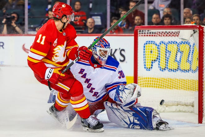 Jan 2, 2020; Calgary, Alberta, CAN; Calgary Flames center Mikael Backlund (11) scores a goal against New York Rangers goaltender Henrik Lundqvist (30) during the first period at Scotiabank Saddledome. Mandatory Credit: Sergei Belski-USA TODAY Sports