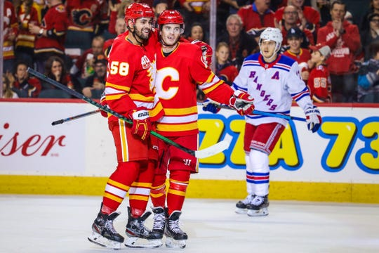 Jan 2, 2020; Calgary, Alberta, CAN; Calgary Flames center Derek Ryan (10) celebrates with defenseman Oliver Kylington (58) after scoring a goal against the New York Rangers during the first period at Scotiabank Saddledome. Mandatory Credit: Sergei Belski-USA TODAY Sports
