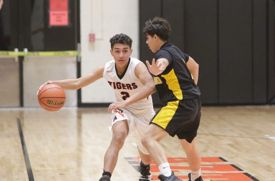 """Aztec's Mason Rios looks to move the ball against Coronado's Anthony Jaramillo during Thursday's """"Rumble in the Jungle"""" tournament opener at Lillywhite Gym in Aztec."""
