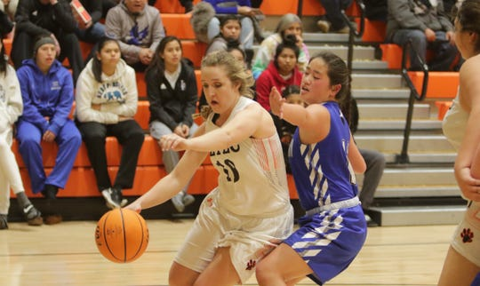 """Aztec's Denym Seabolt attacks the basket against East Mountain's Michelle Carver during Thursday's """"Rumble in the Jungle"""" tournament opener at Lillywhite Gym in Aztec."""