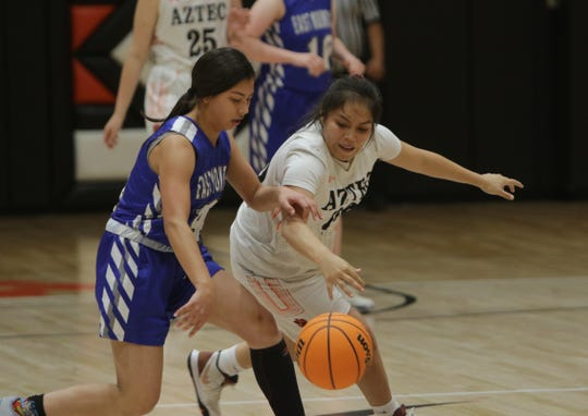 """Aztec's Bessie Davis swipes at the ball and gets a steal against East Mountain during Thursday's """"Rumble in the Jungle"""" tournament opener at Lillywhite Gym in Aztec."""