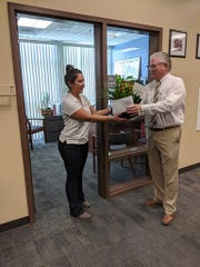 Assistant Superintendent of Business Services Brian Murray surprises Jennifer Mattocks with the announcement of her award.