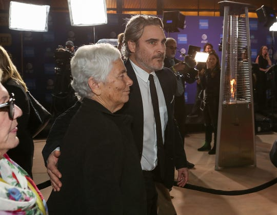 Joaquin Phoenix, left, enters the Palm Springs International Film Festival Awards Gala with his mother Arlyn Phoenix at the Palm Springs Convention Center, January 2, 2020.