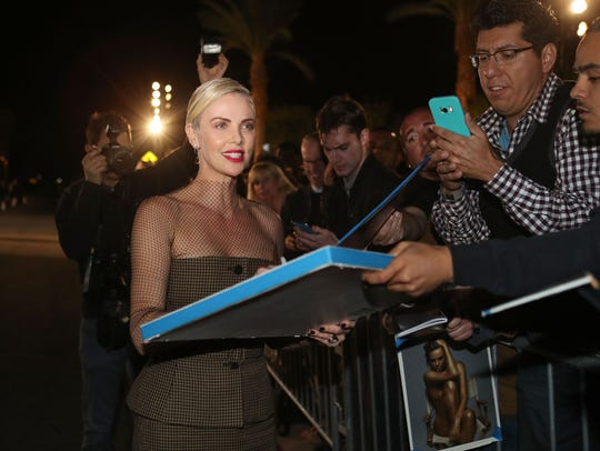Charlize Theron signs autographs for fans at the Palm Springs International Film Festival Awards Gala at the Palm Springs Convention Center, January 2, 2020.