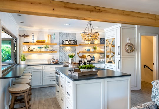 The kitchen is light and bright, with bar seating and a prep island.