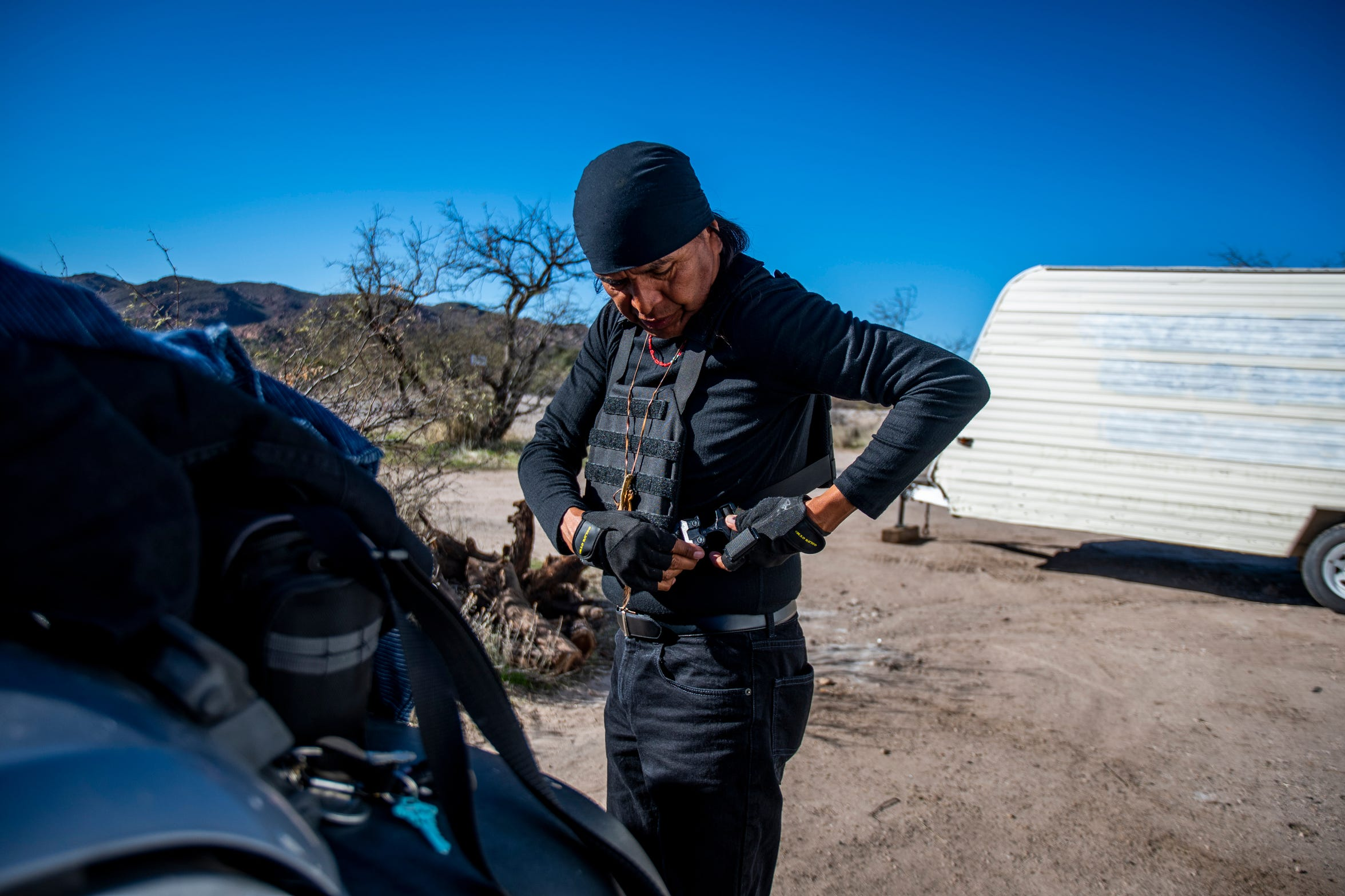 Wendsler Nosie puts on his bullet-proof vest before driving around the area at Oak Flat on Friday, Dec. 20, 2019.