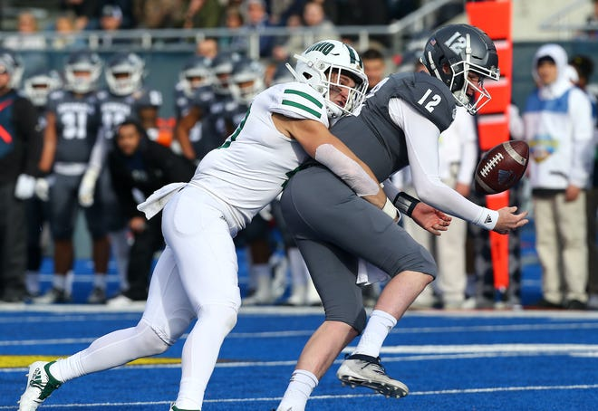 Ohio linebacker Jack McCrory (40) strips the ball from Nevada quarterback Carson Strong during the Famous Idaho Potato Bowl at Albertsons Stadium on Friday.
