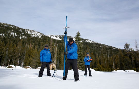Sean de Guzman, center, chief of snow surveys for the California Department of Water Resources, plunges a snow survey tube into the snowpack during the first snow survey of the season at Phillips Station near Echo Summit on Thursday, Jan. 2, 2020. The survey found the snowpack at 33.5 inches deep with a water content of 11 inches which is 97% of average at this location at this time of year. Also seen are DWR's Ramesh Gautam, left, and Lauren Miller.