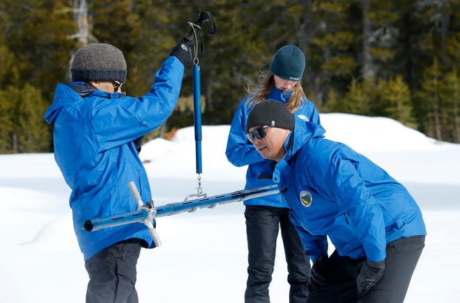 Sean de Guzman, center, chief of snow surveys for the California Department of Water Resources, checks the weight of a snow sample on a scale held by DWR's Ramesh Gautam, left, as DWR's Lauren Miller, background records the information during the first snow survey of the season at Phillips Station near Echo Summit on Thursday, Jan. 2, 2020. The survey found the snowpack at 33.5 inches deep with a water content of 11 inches which is 97% of average at this location at this time of year.