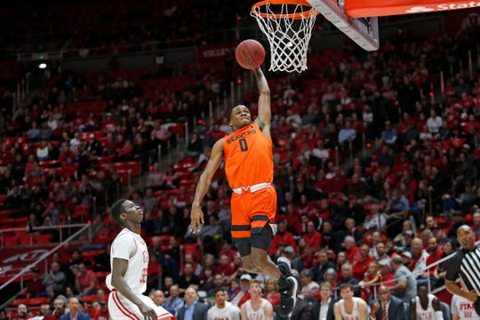 Oregon State guard Gianni Hunt (0) dunks on Utah center Lahat Thioune (32) in the first half during an NCAA college basketball game Thursday, Jan. 2, 2020, in Salt Lake City.