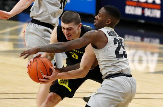 Oregon guard Payton Pritchard, left, fights for control of the ball with Colorado guard McKinley Wright IV in the first half of an NCAA college basketball game Thursday, Jan. 2, 2020, in Boulder, Colo.