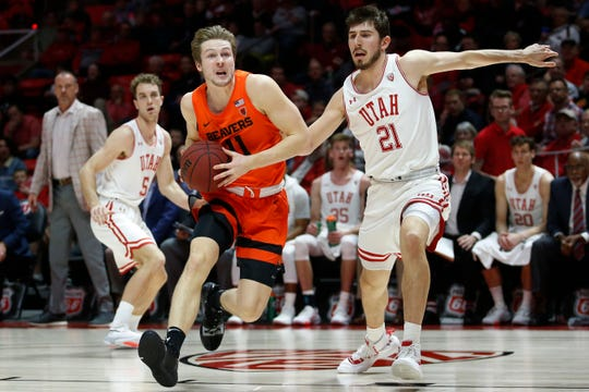 Oregon State guard Zach Reichle (11) drives to the basket as Utah forward Riley Battin (21) defends in the first half during an NCAA college basketball game Thursday, Jan. 2, 2020, in Salt Lake City.
