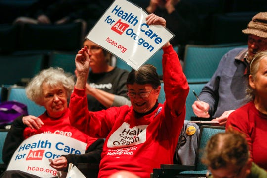 Maryann Beirne holds a sign supporting Medicare for All during a town hall with Sen. Ron Wyden at Chemeketa Community College in Salem, Ore., on Jan. 3, 2020.