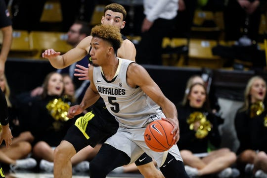 Colorado guard D'Shawn Schwartz, front, drives to the rim past Oregon guard Chris Duarte in the first half of an NCAA college basketball game Thursday, Jan. 2, 2020, in Boulder, Colo.