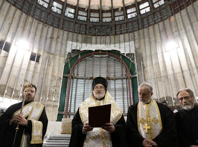 In this Dec. 6, 2019 photo, Greek Orthodox Archbishop Elpidophoros, center, leads clergy in a celebration of St. Nicholas Day inside the St. Nicholas National Shrine at the World Trade Center in New York. Two years after a lack of funds halted construction of the marble-clad Greek Orthodox church, Gov. Andrew Cuomo and Greek Orthodox officials announced plans Thursday, Jan. 2, 2020, to resume construction with the goal of finishing the rebuilding by the 20th anniversary of the terrorist attacks of Sept. 11, 2001.