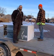Rowdy Olson (right) and Dallas Kubik help deliver a refrigerator that was donated to Heavenly Helpers on the Highway.
