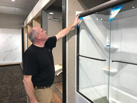 Steve Swenson, owner of Handy Man Home Remodeling Center, examines some of his product. The store is planning a grand opening event for Jan. 18, with deals for customers as part of a scratch-and-dent sale.