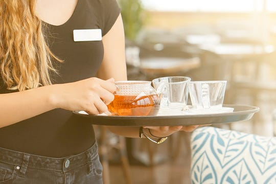 A waitress delivers tea in this stock photo.