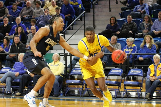 Doug Wilson looks to drive past Kevin Obanor of Oral Roberts Thursday night at Frost Arena