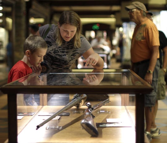 Melissa Huckleberry looks at firearms in a display case with her son Brody, 9, at the NRA National Sporting Arms Museum at Bass Pro Shops on Friday, August 2, 2013.
