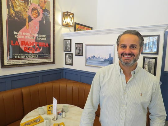 """Surrounded by family photos and a favorite movie poster, the back table at Immigrant Son Caffe in Ventura is semi-reserved for drop-in visits by Giovanni Tromba, the father of owner Alessandro Tromba. """"But he really prefers to sit at the bar,"""" the younger Tromba says with a laugh."""