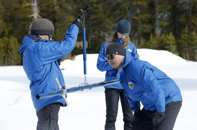 Sean de Guzman, center, chief of snow surveys for the California Department of Water Resources, checks the weight of a snow sample on a scale held by DWR's Ramesh Gautam, left, as DWR's Lauren Miller, background records the information during the first snow survey of the season at Phillips Station near Echo Summit, Calif., Thursday, Jan. 2, 2020. The survey found the snowpack at 33.5 inches deep with a water content of 11 inches which is 97% of average at this location at this time of year.