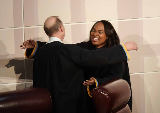 The Honorable Tamika Montgomery-Reeves gives hugs to members of the Supreme Court of Delaware after she was publicly sworn in for her first term as a Justice of the Delaware Supreme Court making her the first African-American justice in Delaware history, Friday at Howard High School.