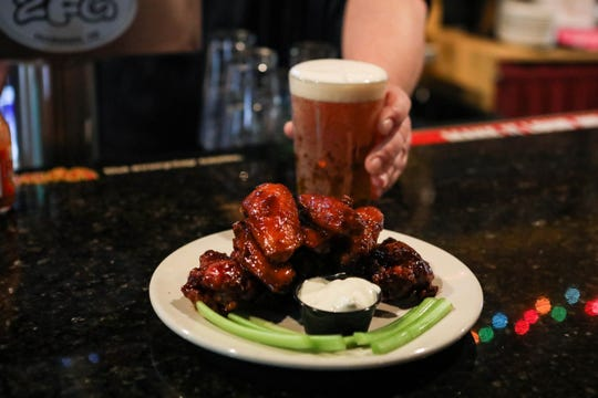A plate of 'triple play' flavored chicken wings feature mild, bourbon barbecue and poached pear molasses sauce at 2 Fat Guys restaurant in Hockessin.