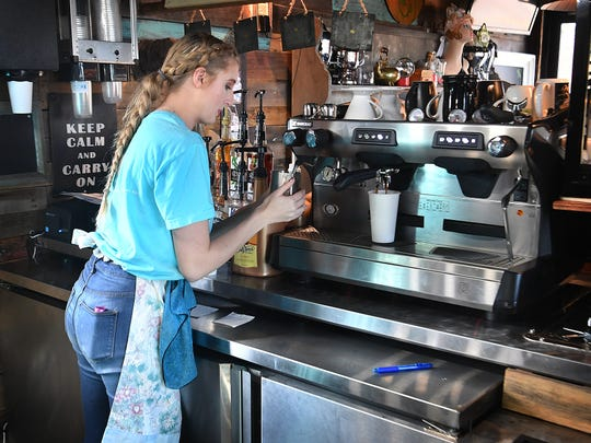 Amarra Horn, a barista for Hobo Coffee and Ice Company, makes a latte at the new coffe shop on Seymour Highway. The business was built from three modified shipping containers.