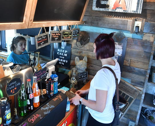 Alyssa Rutledge of Hobo Coffee and Ice Company takes an order from customer Sarah Ostermann Friday morning. The new coffee shop offers a variety of coffees, lattes, cappuccinos and frappes as well as pastries, cinnamon rolls and cake bites.