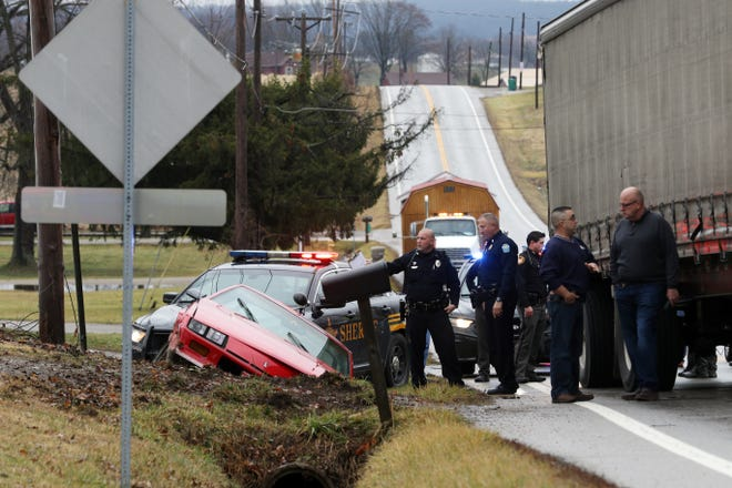 Law enforcement officers investigate the scene on Frazeysburg Road after a crash Friday afternoon. Police were pursuing a vehicle when it crashed in a ditch just north of Olde Falls Road.