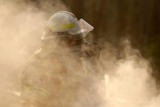 A firefighter covers his face from block smoke as he battles a fire near Bendalong, Australia, Friday, Jan. 3, 2020. (AP Photo/Rick Rycroft)