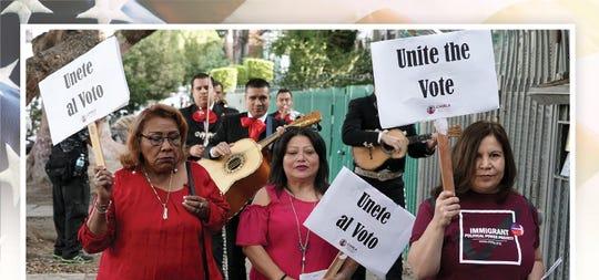 """Votantes latinos con pancartas que rezan """"Unidos por el Voto""""  recibieron una serenata con mariachis camino a sus centros de votación  para participar en la elección general del 2018 en Los Angeles, California, el 6 de noviembre del 2018."""