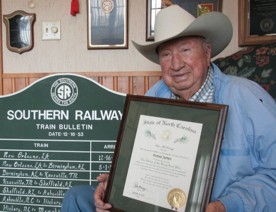 Forrest Jarrett displays his Order of the Long Leaf Pine proclamation in the railroad room at his home in Leicester.