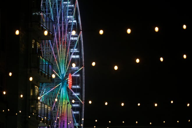 The Skystar Wheel lights up as it spins into the evening during the Snow Banks at The Bank event on Freedom Way in downtown Cincinnati on Friday, Jan. 3, 2020.