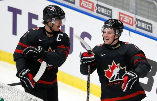 Canada's Alexis Lafreniere, right, celebrates with Canada's Barett Hayton, left, after scoring a goal against Finland in a semifinal at the world junior championship in Ostrava, Czech Republic.