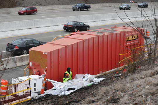 Crews work on pumping out foreign material into a Frac-Tank along east bound I-696 down the hill from a condemned building containing toxic material in Madison Heights.