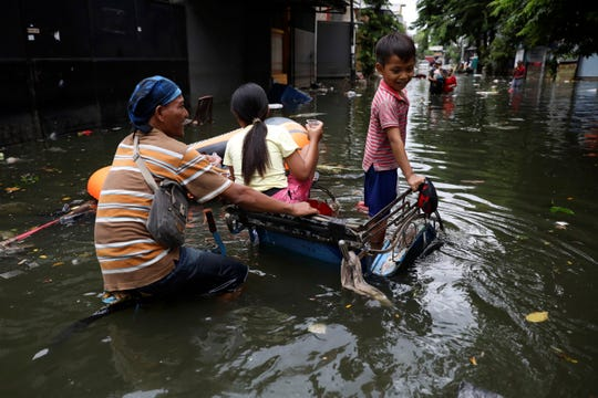 A young boy reacts as he rides on a tricycle with his father and sister at a flooded neighborhood in Jakarta, Indonesia, Saturday, Jan. 4, 2020.