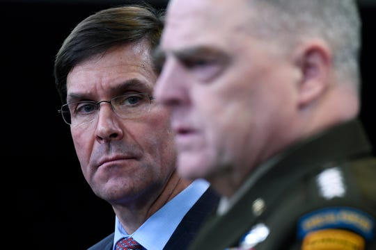 Defense Secretary Mark Esper, left, listens as Joint Chiefs Chairman Gen. Mark Milley, right, speaks during a news conference at the Pentagon in Washington, Friday, Dec. 20, 2019.