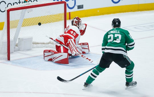 Dallas Stars defenseman Esa Lindell (23) watches as Detroit Red Wings goaltender Jonathan Bernier (45) gives up a goal to Stars forward Roope Hintz during the first period of an NHL hockey game.
