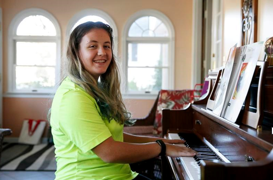 "Grace Brown, 14, poses for a portrait by the piano at her home in Alexandria, Va., Friday, Nov. 1, 2019. Brown chose to take ""online PE,"" utilizing a fitness tracker, so that she could participate in a piano lab as an extra elective."