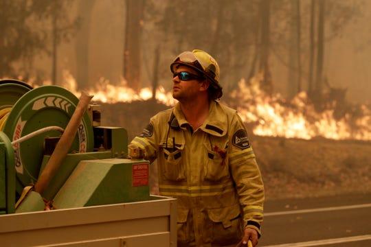 A Forest Corporation worker manages a fire hose as he battles a fire near Moruya, Australia, Saturday, Jan. 4, 2020.