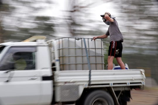 A man stands in the back of a truck as they patrol a fire at Batemans Bay, Australia, Saturday, Jan. 4, 2020.