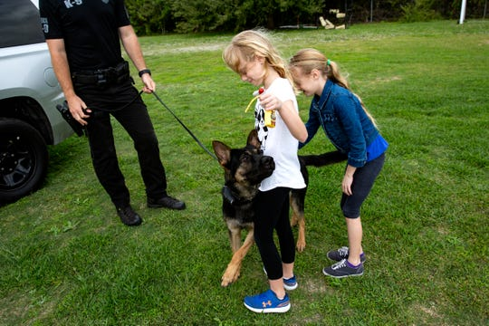 Ryland King, 8, left, and her sister McKinley King, of Sarasota, play with Bear a 1-year old K-9 in training as his handler Drake Sunderland with North Port Police Departments looks on during the 3rd annual Florida Gulf Coast Police K-9 Competition hosted by the Cape Coral Police Department, Saturday, Jan. 4, 2020, at Island Coast High School in Cape Coral.