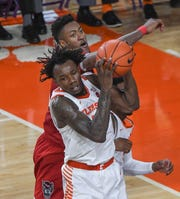 Clemson guard Tevin Mack(13) rebounds near North Carolina State forward Manny Bates during the first half at Littlejohn Coliseum Saturday, January 4, 2020.