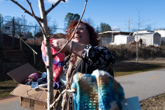 Joan Milazzo-Mendez hangs hats and scarves along the Swamp Rabbit Trail Saturday, Jan. 4, 2020.